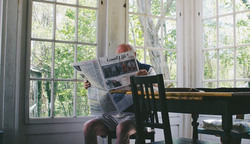 man reading the paper in a large dining room