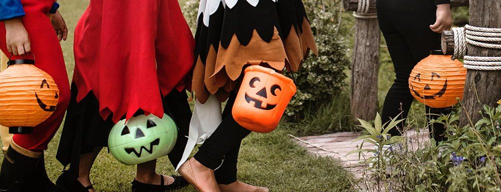 people carrying jack-o-lantern buckets