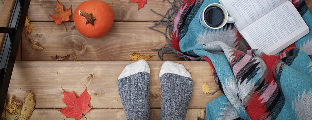 person wearing socks standing on steps with leaves and pumpkin