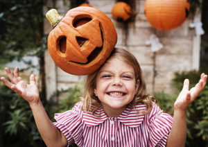 smiling girl with a jack-o-lantern on her head