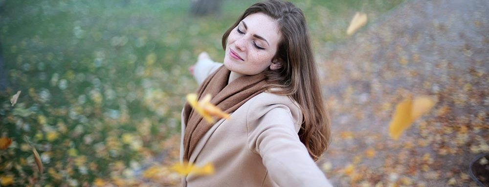 woman in a park with fall leaves
