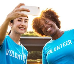 women snapping a selfie in volunteer t-shirts