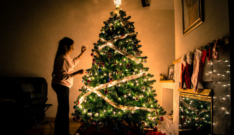 woman decorating a Christmas tree in low light