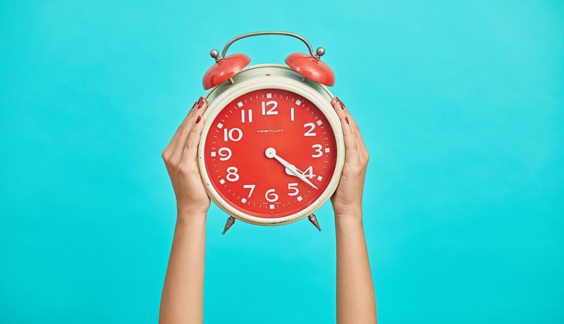 an alarm clock held up by two hands