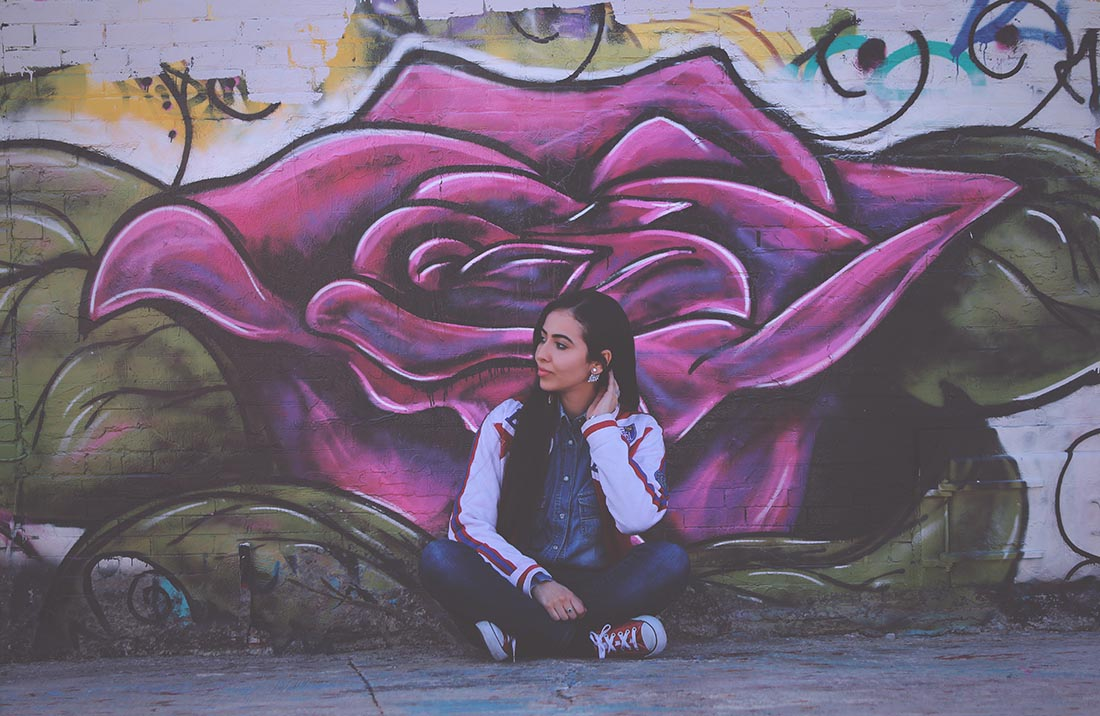 young woman sitting in front of a mural
